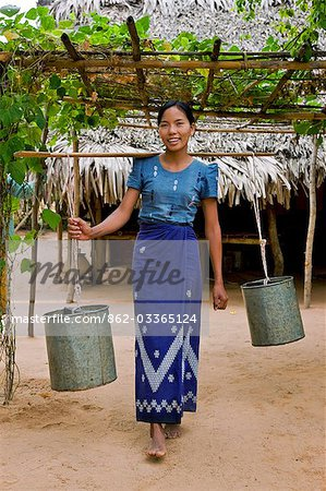 Myanmar. Burma. Bagan. A girl carries water to a thatched house in Taungzin. Stock Photo - Rights-Managed, Image code: 862-03365124
