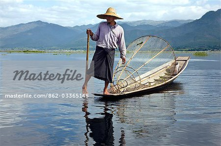 Myanmar. Burma. Lake Inle. An Intha fisherman with a traditional fish trap uses an unusual leg-rowing technique to propel his flat-bottomed boat across the lake while standing. Stock Photo - Rights-Managed, Image code: 862-03365145