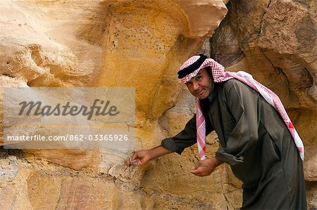 Jordan,Petra,El Mraibet. A local beduin guide points out some of the intricate geology of the sandstone deposits near the Nabeatean capital of Petra. Stock Photo - Rights-Managed, Image code: 862-03365926