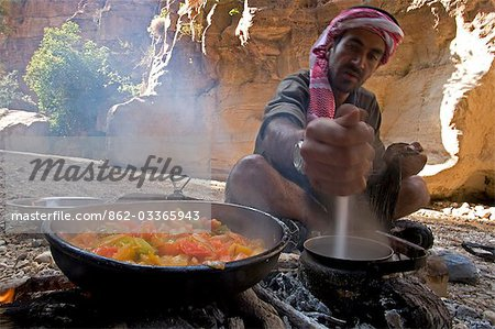 Jordan,Petra,Wadi Daphna. A local beduin guide dressed in traditional clothing prepares a lunch time meal over an open fire in the dead chasm within Wadi Daphna. Stock Photo - Rights-Managed, Image code: 862-03365943