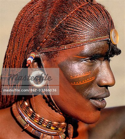 A Samburu warrior resplendent with long,braided,Ochred hair. The round ear ornaments of the warriors are fashioned from ivory. Samburu warriors are vain and proud,taking great trouble over their appearance. Ochre is a natural earth containing ferric oxide which is mixed with animal fat to the consistency of greasepaint. Stock Photo - Rights-Managed, Image code: 862-03366036