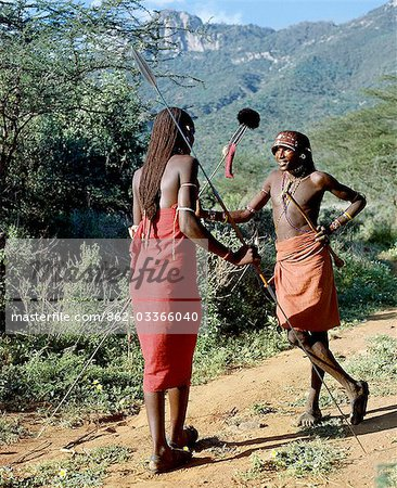 Two Samburu warriors converse,their long braids of Ochred hair distinguishing them from other members of their society. Samburu warriors are vain and proud,taking great trouble over their appearance. An ostrich feather pompom decorates the top of a spear. Stock Photo - Rights-Managed, Image code: 862-03366040