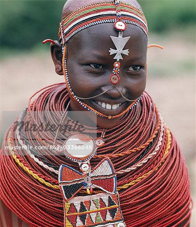 Samburu girls are given strings of beads by their fathers when they are still young. As soon as they are old enough to have lovers from the warrior age-set,they regularly receive gifts from them. Over a period of years,their necklaces can smother them up to their necks. The metal cross-like ornament hanging from the girl's headband has no religious significance. Stock Photo - Rights-Managed, Image code: 862-03366046