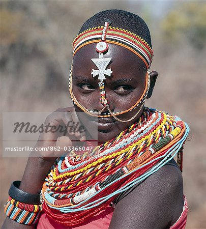 Samburu girls are given strings of beads by their fathers when they are still young. As soon as they are old enough to have lovers from the warrior age-set,they regularly receive gifts from them. Over a period of years,their necklaces can smother them up to their necks. The metal cross-like ornament hanging from the girl's headband has no religious significance. Stock Photo - Rights-Managed, Image code: 862-03366047