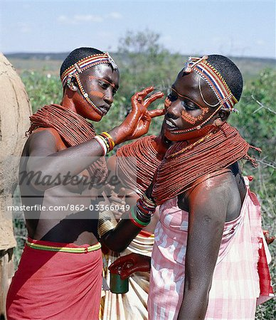 Samburu girls paint each others faces with abstract designs in readiness for a dance. Already,their necks and beaded necklaces have been coated with red ochre. Only girls and warriors decorate their faces; the orange powder they use is called blue. Stock Photo - Rights-Managed, Image code: 862-03366049