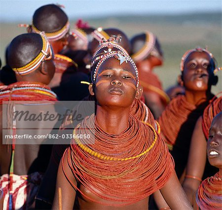Young Samburu girls dance during a wedding celebration. By arching their backs and thrusting out their chests,they flick their beaded necklaces up and down while dancing silently to the songs of the warriors. Their bodies and necklaces have been smeared with red ochre. Stock Photo - Rights-Managed, Image code: 862-03366050