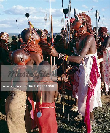 During Samburu wedding celebrations,warriors resplendent with long Ochred braids dance with young girls who have put on all their finery for the occasion. Both warriors and girls smear their faces,necks and shoulders with red ochre mixed with animal fat to enhance their appearance. Two spears are tipped with ostrich-feather pompoms. Stock Photo - Rights-Managed, Image code: 862-03366058