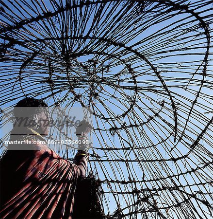 A Turkana woman makes the final ties to the dome-shaped framework of her home. In wet weather,hides will be laid on top and secured with leather thongs. Stock Photo - Rights-Managed, Image code: 862-03366098