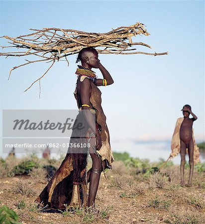 In the semi-arid terrain of Turkanaland,women have to travel great distances to collect firewood. Like other Nilotic people,Turkana women balance heavy loads on their heads with graceful carriage and poise. The attire of this woman is typical of married women in the tribe. Stock Photo - Rights-Managed, Image code: 862-03366108
