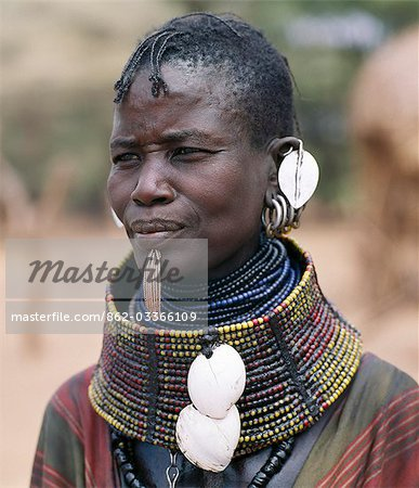 A Turkana woman wears all the finery of her tribe: brass lip plug,beaded collar decorated with bleached shells of the African land snail,leaf-like ear ornaments and metal earrings from which hang tiny rings of goat horn. Stock Photo - Rights-Managed, Image code: 862-03366109