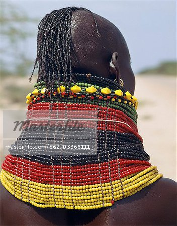 A Turkana girl's necklaces are well-oiled with animal fat and glisten in the sun. Occasionally,a girl will put on so many necklaces that her vertebrae stretch and her neck muscles gradually weaken. The partially shaven head is typical of Turkana women and girls. Stock Photo - Rights-Managed, Image code: 862-03366111