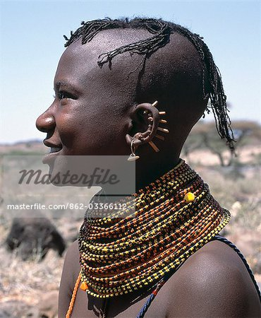 A young Turkana girl has had the rims of her ears pierced in seven places and keeps the holes open with small wooden sticks. After marriage,she will hang leaf-shaped metal pendants from each hole. Stock Photo - Rights-Managed, Image code: 862-03366112