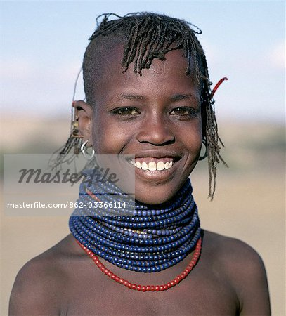 A pretty young Turkana girl has already had the flesh below her lower lip pierced in readiness for a brass ornament after her marriage. The rims of her ears have also been pierced and the holes kept open with small wooden sticks. Stock Photo - Rights-Managed, Image code: 862-03366114