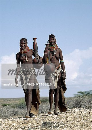 Two Turkana girls set off to fetch water from a nearby Waterhole. Their water containers are made of wood by the women of the tribe. Their 'V' shaped aprons are made of goatskin and have been edged with hundreds and hundreds of round discs fashioned out of ostrich eggshells. Stock Photo - Rights-Managed, Image code: 862-03366116