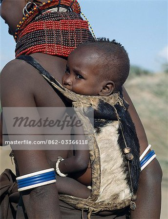 When a Turkana woman gives birth,four goats will be slaughtered in a twenty-four-hour period to celebrate the occasion. The skin of the first goat will be made into a pouch for carrying the baby on its mother's back. The small wooden balls on the back of this pouch are charms to ward off evil spirits. The baby is wearing a bracelet of ostrich eggshell beads. Stock Photo - Rights-Managed, Image code: 862-03366118