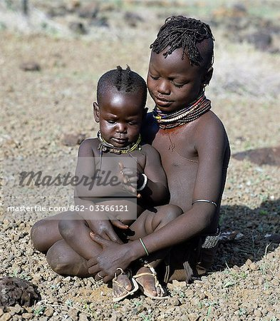 Childhood is brief in nomadic communities. From an early age,Turkana girls help their mothers with the household chores and look after their younger brothers and sisters during the day. The baby has wooden charms round her neck to ward off evil spirits. Stock Photo - Rights-Managed, Image code: 862-03366121