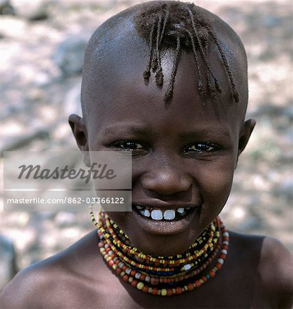 A young Turkana girl with her head shaved except for a tuft,which is braided. This is the usual hairstyle for women and girls. Stock Photo - Rights-Managed, Image code: 862-03366122