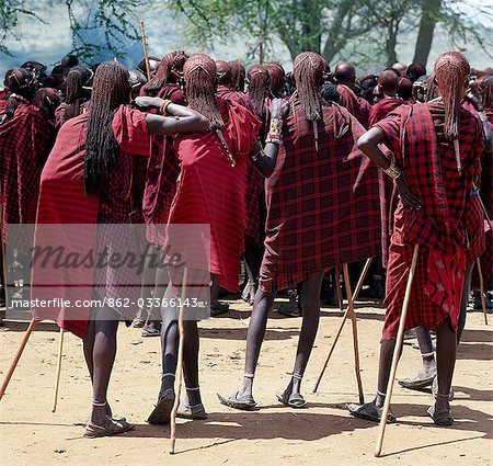 Maasai warriors resplendent with long ochred braids relax and wait for the start of a ceremony. Red has always been their preferred colour. Stock Photo - Rights-Managed, Image code: 862-03366143