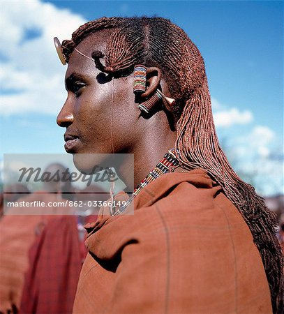 Kenya,Kajiado,Maparasha. A Maasai warrior resplendent with long,ochred braids. This singular form of hairstyle distinguishes warriors from the rest of their society. This man has looped his elongated and decorated earlobes over his ears - a common practice when walking through thorn scrub country to prevent the loops being snagged by thorns. Stock Photo - Rights-Managed, Image code: 862-03366149