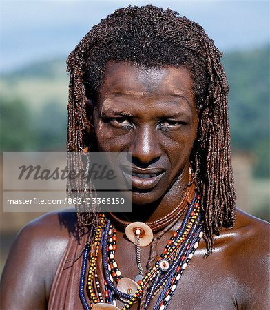 A Maasai warrior resplendent with long ochred braids. His body has been smeared with red ochre mixed with animal fat while parts of his face have been covered with ochre powder. Stock Photo - Rights-Managed, Image code: 862-03366150