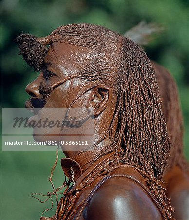 A Maasai warrior has daubed himself with red ochre mixed with animal fat to participate in a dance. His long ochred braids have been drawn forward from the crown of the head and tied in three places. This singular hairstyle sets warriors apart from the rest of their society. Stock Photo - Rights-Managed, Image code: 862-03366151