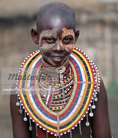 A young Maasai girl wears face paint and numerous beaded ornaments in preparation for a dance with warriors. Stock Photo - Rights-Managed, Image code: 862-03366170