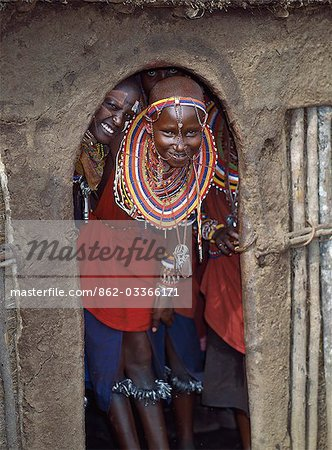 Maasai girls in all their finery and with bells tied round their legs wait at the entrance to a house before dancing with warriors. Stock Photo - Rights-Managed, Image code: 862-03366171