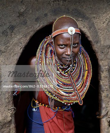 A young Maasai girl in all her finery pauses at the entrance to her mother's home. The wall and roof of the house are plastered with a mixture of cow dung and soil. Stock Photo - Rights-Managed, Image code: 862-03366172