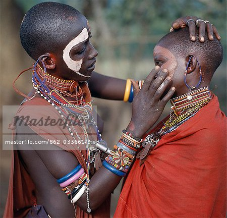 Young Maasai girls decorate their faces with ochre and clay in preparation for a dance. Stock Photo - Rights-Managed, Image code: 862-03366173