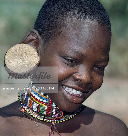 A young Maasai girl wearing a wooden plug in her pierced ear to elongate the earlobe. It has been a tradition of the Maasai for both men and women to pierce their ears and elongate their lobes for decorative purposes. Her two lower incisors have been removed - a common practice that may have resulted from an outbreak of lockjaw a long time ago. Stock Photo - Rights-Managed, Image code: 862-03366174