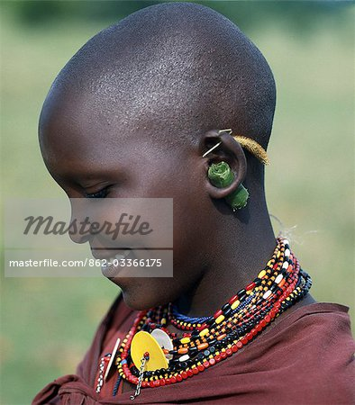 A young Maasai girl keeps the holes in her pierced ears from closing with grass and rolled leaves. She will gradually stretch her earlobes by inserting progressively larger wooden plugs. By tradition,both Maasai men and women pierce and elongate their earlobes for decorative purposes. Stock Photo - Rights-Managed, Image code: 862-03366175