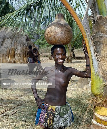 A Giriama girl from Kenya's Coast Province carrying a gourd full of water on her head. Her small skirt is made from strips of printed cotton material. Stock Photo - Rights-Managed, Image code: 862-03366188