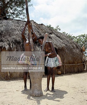 Two Giriama girls pound corn outside their home using a large wooden mortar and pestles. Their small skirts are made from strips of printed cotton material - a traditional dress of Giriama women and children. Stock Photo - Rights-Managed, Image code: 862-03366189