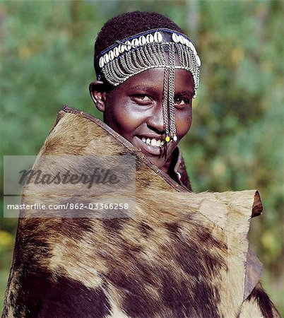 A girl from the Ogiek community of hunter-gathers living in the Mau Forest keeps warm in a cowhide. Following Maasai custom,she wears a decorated headband which marks her recent circumcision. Stock Photo - Rights-Managed, Image code: 862-03366258