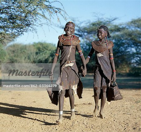 Two jovial Pokot girls set off with leather bags in search of edible berries. Pokot girls and women traditionally wore leather skirts and capes made from home-tanned goatskins. The necklaces of young girls are made from small segments of sedge grass. Stock Photo - Rights-Managed, Image code: 862-03366279