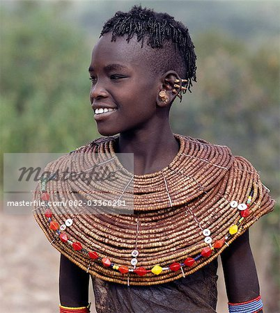 A young Pokot girl in traditional attire. Girls wear leather skirts and capes made from home-tanned goatskins. Her broad necklaces are made from small segments of sedge grass. Her ears have already been pierced in four places,ready to insert the large brass earrings she will acquire after marriage. Stock Photo - Rights-Managed, Image code: 862-03366281
