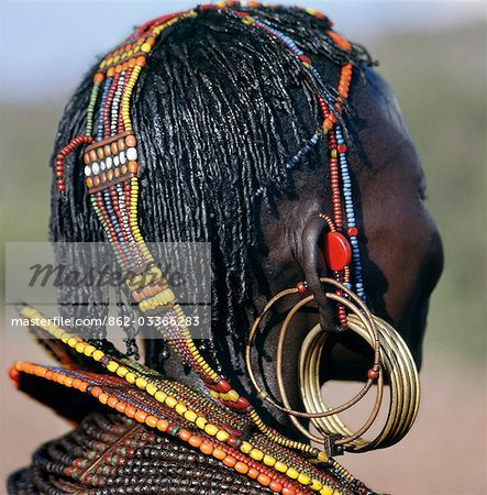 A close-up of a Pokot woman's earrings,hairstyle and beaded ornaments. Only married women wear brass earrings and glass-beaded collars. The band over her head supports the weight of her heavy earrings. Stock Photo - Rights-Managed, Image code: 862-03366283