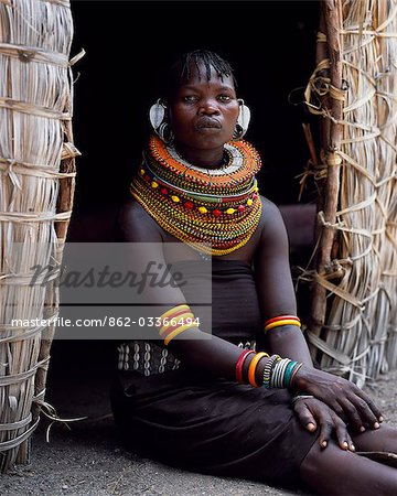A Turkana woman,typically wearing many layers of bead necklaces and a series of hooped earrings with an pair of leaf-shaped earrrings at the front,sits in the entrance to her hut. Stock Photo - Rights-Managed, Image code: 862-03366494