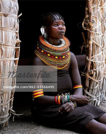 A Turkana woman,typically wearing many layers of bead necklaces and a series of hooped earrings with an pair of leaf-shaped earrrings at the front,sits in the entrance to her hut. Stock Photo - Rights-Managed, Image code: 862-03366495