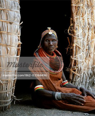 A Turkana woman sitting in the doorway of her hut. Her heavy mporro braided necklace identifies her as a married woman. Typical of her tribe,she wears many layers of bead necklaces and a beaded headband. Stock Photo - Rights-Managed, Image code: 862-03366496