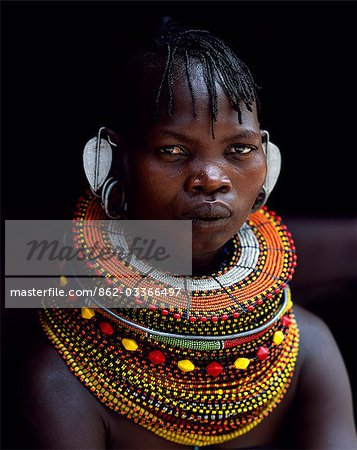 A Turkana woman sitting in the doorway of her hut. Her heavy mporro braided necklace identifies her as a married woman. Typical of her tribe,she wears many layers of bead necklaces and a beaded headband. Stock Photo - Rights-Managed, Image code: 862-03366497