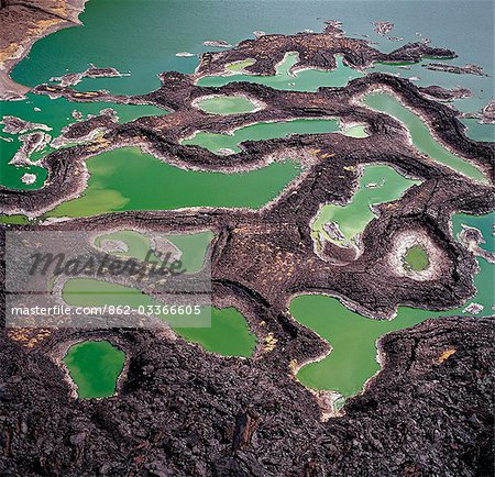 A series of lava rock pools are situated just off the southern end of Lake Turkana,northern Kenya's Jade Sea. The colour of the water is caused by extreme alkalinity in which green algae with a high chlorophyll content grows. Stock Photo - Rights-Managed, Image code: 862-03366605