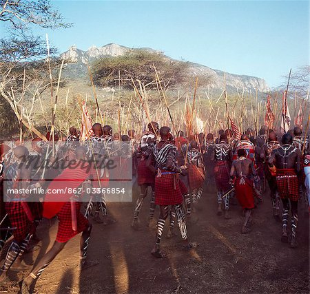 Africa,Kenya,Kajiado District,Ol doinyo Orok. A large gathering of Maasai warriors dance with raised sticks after they return from daubing themselves with white clay during an Eunoto ceremony when the warriors become junior elders and thenceforth are permitted to marry Stock Photo - Rights-Managed, Image code: 862-03366854
