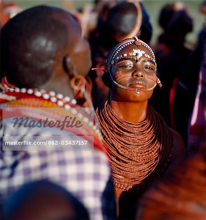 A young Samburu girl dances during a wedding celebration. By arching her back and thrusting out her chest,she flicks her beaded necklaces up and down while dancing silently to the songs of the warriors. Her body and necklace have been smeared with red ochre,and her eyebrows blackened with charcoal dust mixed with animal fat. Stock Photo - Rights-Managed, Image code: 862-03437157