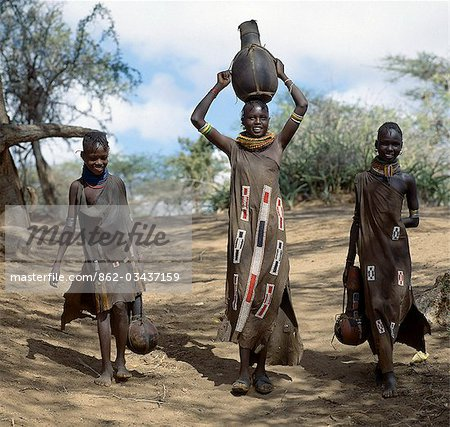 Turkana girls return home from a Waterhole with water containers made of wood. Their cloaks are goatskin embellished with glass beads. Stock Photo - Rights-Managed, Image code: 862-03437159