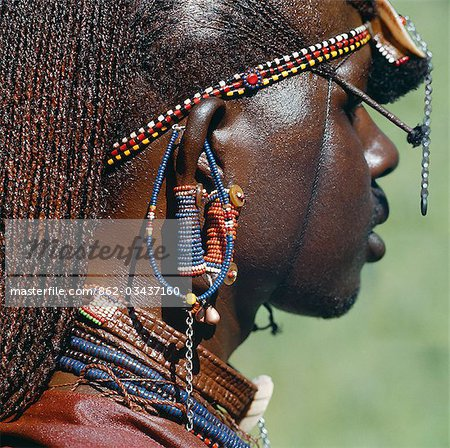 Detail of a Maasai warrior's ear ornaments and other beaded or metal adornments. The Maasai practice of piercing ears in adolescence and gradually elongating the lobes is gradually dying out. This warrior's body and his long braids have been smeared with red ochre mixed with animal fat. Stock Photo - Rights-Managed, Image code: 862-03437160