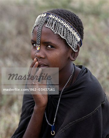 A young Maasai girl wears a headband decorated with chains and cowrie shells that signifies her recent circumcision. Clitodectomy was commonly practiced by the Maasai but it is now gradually dying out. Stock Photo - Rights-Managed, Image code: 862-03437161