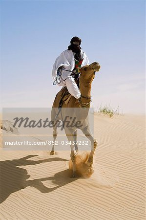 Mali,Timbuktu. In the desert north of Timbuktu,a Tuareg man rides his camel across a sand dune. He steers the animal with his feet. Stock Photo - Rights-Managed, Image code: 862-03437232