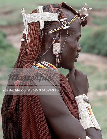 A warrior of the Kisongo section of the Maasai with his long Ochred braids decorated with beaded ornaments. His broad armulet is typical of the Kisongo living in northern Tanzania where white is the preferred colour of their beadwork. Stock Photo - Rights-Managed, Image code: 862-03437401