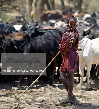 A young Maasai herdsboy controls his family's cattle at the Sanjan River to prevent too many animals watering at the same time. Stock Photo - Rights-Managed, Image code: 862-03437402